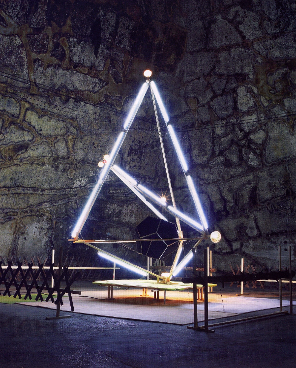 Deuterium Attenzione, 2001/2006, Holz, Neonlampen, Glühbirnen, Teppich, Styropor, Fichtenstämme, Jägerzaun, 600 × 700 × 500 cm, Installationsansicht »Supernova«, Domaine Pommery, Reims, 2006, Courtesy FRAC PACA, Marseille, photo: Laurent Montaron und Aurélien Froment