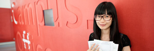 asian student in front of a red wall
