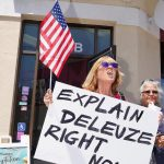 "Person holding a sign: ""Explain Deleuze right now""."