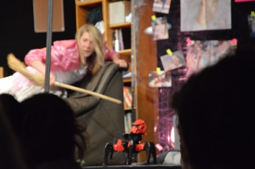 Actress hitting the robot with a stick .