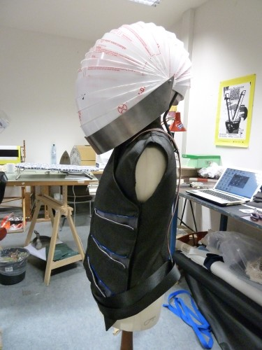 side view finished vest and helmet (protective coat still on); basic wire frame structure for O² pack, that holds up helmet